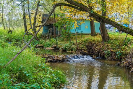 Autumn landscape with flowing river and fallen leaves Stock Photo