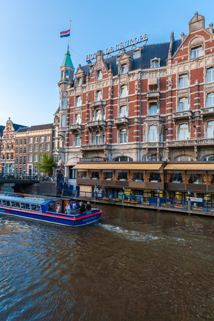 AMSTERDAM, NETHERLANDS - APRIL 3, 2008: Luxury hotel Europe on the banks of the Amstel river and the boats Editorial