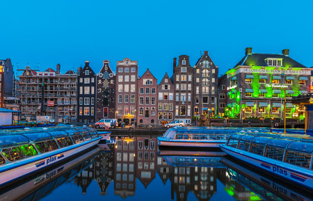tour boats: AMSTERDAM, NETHERLANDS - APRIL 3, 2008: Tour boats and dancing houses along the Damrak canal illuminated by night light Editorial