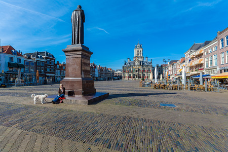 DELFT, NETHERLANDS - APRIL 4, 2008:  A young girl with a dog sitting on a monument to the Dutch lawyer Hugo Grotius