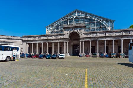 mondial: BRUSSELS, BELGIUM - APRIL 5, 2008: Tourists walk in front of Entrance to the Palais Mondial (South Hall), housing AutoWorld vintage car museum in Cinquantenaire Park Editorial