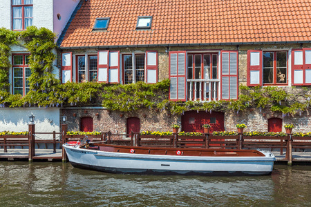 BRUGES, BELGIUM - APRIL 6, 2008: Boat on the dock in front of a vintage house channel Dijver Editorial