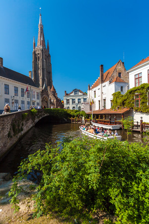 BRUGES, BELGIUM - APRIL 6, 2008: Tourists float on a boat through the channel near  Dijver bridge and Church of Our Lady Editorial