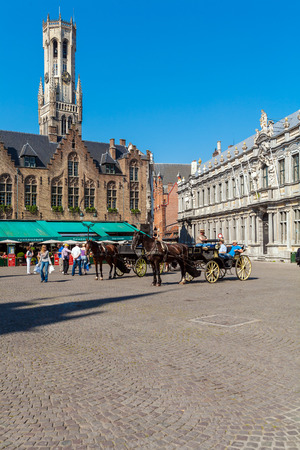 BRUGES, BELGIUM - APRIL 6, 2008: Tourists ride in traditional horse-drawn carriage on the Grote Markt in front of the  Provinciaal Hof Editorial