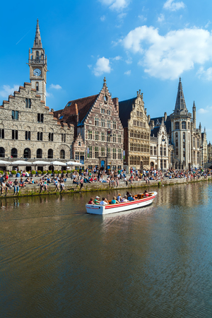 tour boats: GHENT, BELGIUM - APRIL 6, 2008: Tour boats and students sitting on the waterfront of river Leie along Graslei street