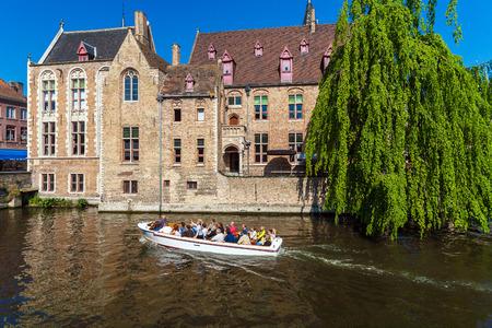 BRUGES, BELGIUM - APRIL 6, 2008: Tourists float on a boat through the Dijver channel near vintage homes