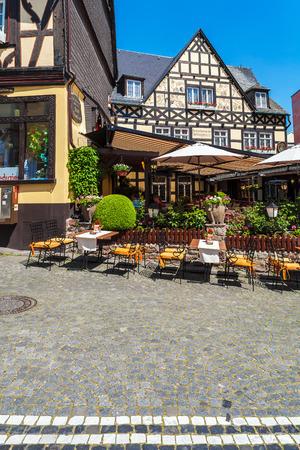 RUDESHEIM ON RHEIN, GERMANY - APRIL 8, 2008:  Street restaurant and vintage Fachwerk homes