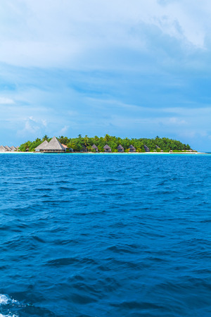 horizont: Small atoll island with traditional wooden bungalows and Indian ocean, Maldives