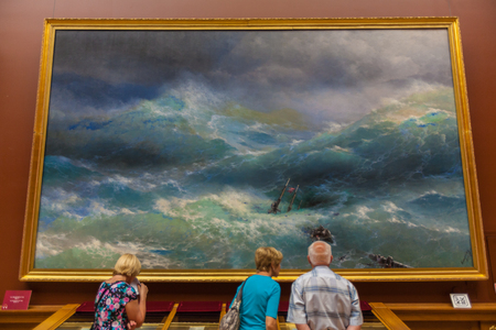 ninth: SAINT PETERSBURG, RUSSIA - JULY 26, 2014:  Visitors in front of the painting the Ninth wave by Ivan Aivazovsky Editorial