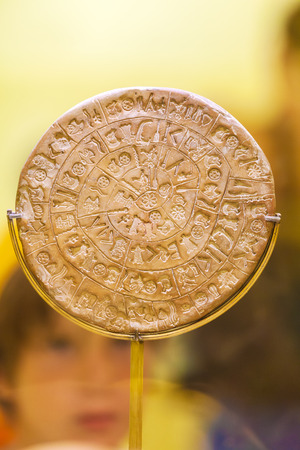 HERAKLION, GREECE - AUGUST 3, 2012: Tourists exploring the exhibition of Archaeological Museum of Heraklion from the Phaistos disk in the foreground