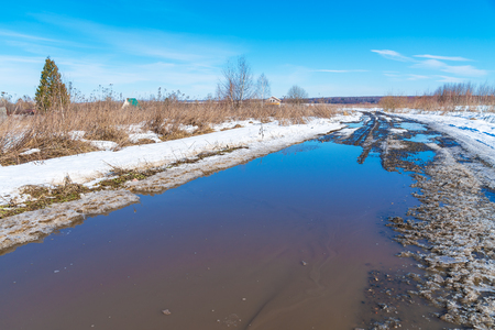thawed: The road during the spring thaw with mud and puddles Stock Photo