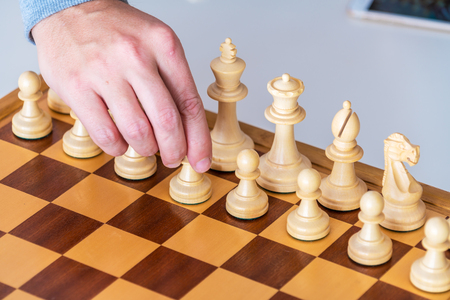 battle plan: The beginning of the game - the hand with the pawn makes the first move on the chess Board Stock Photo