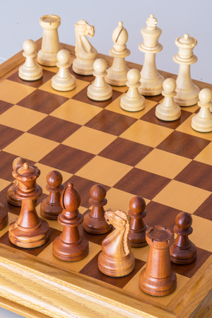 Chess pieces in starting position on a wooden oak Board Stock Photo