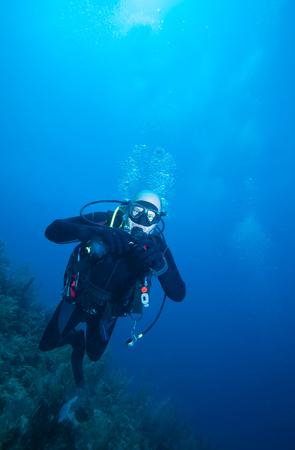 Happy young scuba diver swimming near coral reef, Cuba   Stock Photo