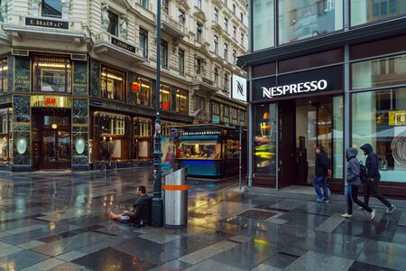 Vienna, Austria - October 22, 2017: A homeless beggar asks for alms in the center of the old town next to the Nespresso coffee shop