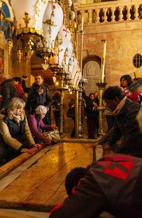 Jerusalem, Israel - February 16, 2013: Pilgrims praying near Stone of Unction at entrance in Church of the Holy Sepulchre Redakční