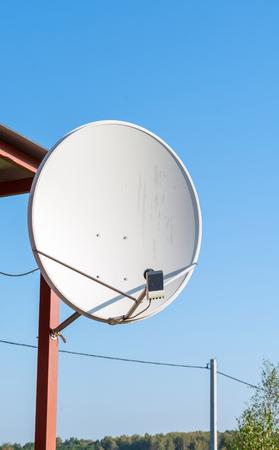 Large gray satellite dish antenna on the garden house pillar