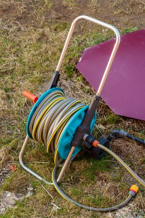 Red waterhole caisson hatch and reel with green garden watering hose