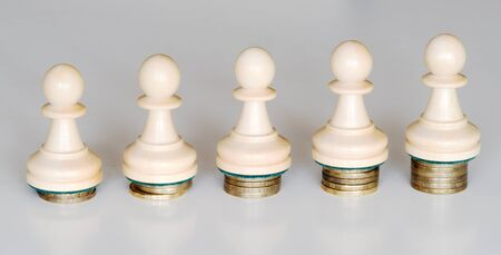 Five wood pawns of chess pieces on columns of coins symbolizing a slight income inequality