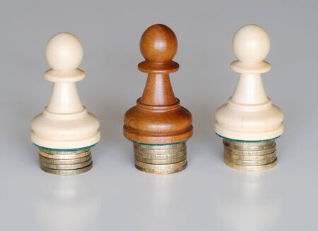 Three wood pawns chess pieces on columns of coins, symbolizing the equality of income