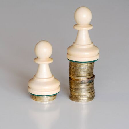 Two wood pawns chess pieces on columns of coins, symbolizing a sharp income inequality
