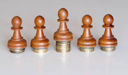 Five wood pawns of chess pieces on columns of coins symbolizing the exclusion from equal income Banco de Imagens