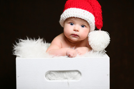 a christmas baby sitting in a white wooden box wearing a red tailed hat