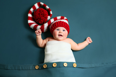cute joyful christmas baby in a red and white gnome long-tailed hat lying in a big pocket
