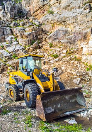 cargador frontal: Amarillo máquina pala cargadora recogiendo grandes piedras en una cantera Foto de archivo