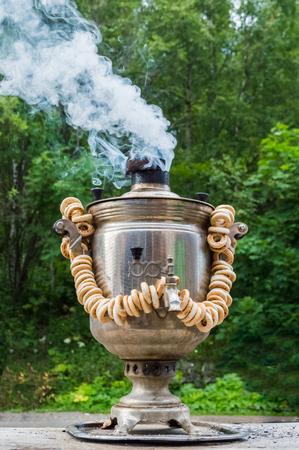Traditional old Russian tea kettle samovar boiling at nature