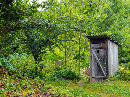 Old wooden toilet Camping in a village among the trees and bushes