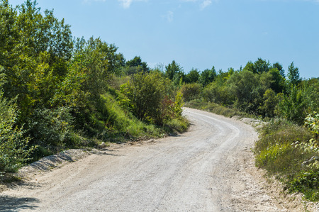 Dirt road leading over a high mountain pass in daytime Stock Photo