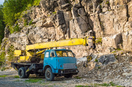 telescopic: Old yellow automobile crane with blue cab and telescopic boom in transport position near with rocky mountain Stock Photo