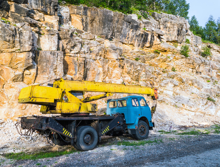 telescopic: Old yellow automobile crane with blue cab and telescopic boom in transport position near with rocky mountain, left rear coner view