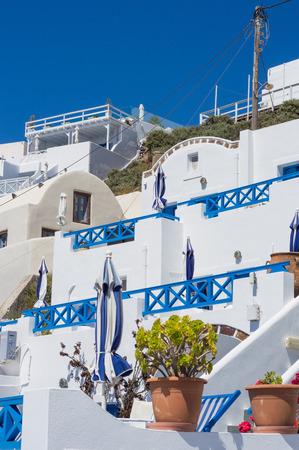 greek pot: casa greca con terrazza sulla collina. Vaso di fiori in primo piano. architettura bianco sull'isola di Santorini, in Grecia Archivio Fotografico
