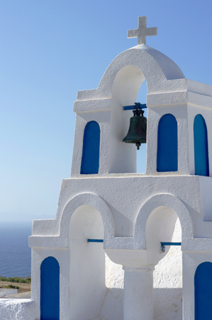 White church tower with three bells against blue sky background in Oia village, Santorini island, Greece