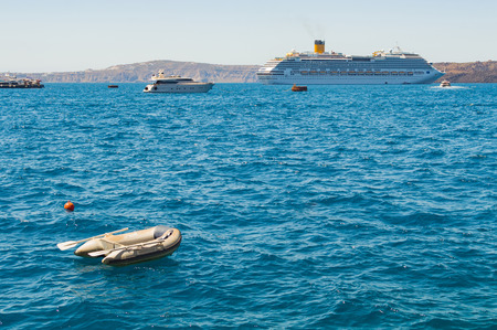 Dinghy boat mooring at Santorini island. Luxury cruise ship on background. Waiting for the host.