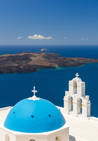 Blue-domed chapel with ochre bell tower in Oia, Santorini, Greece, with ocean behind