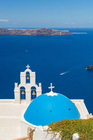 ochre: Blue-domed chapel with ochre bell tower in Oia, Santorini, Greece, with ocean behind