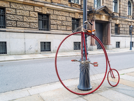 original bike: Old High wheeler bicycle propped and tied to a pole on the streets of the city of Dresden, Germany
