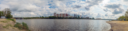 The sandy shore of the lake, panoramic view of picturesque clouds in the sky. nasty weather windy day.