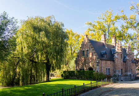rive: The cute old traditional brick house in Brugge. Willow tree near building. small Belgian town Stock Photo