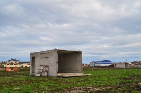 An abandoned concrete box in the field is used as a house.