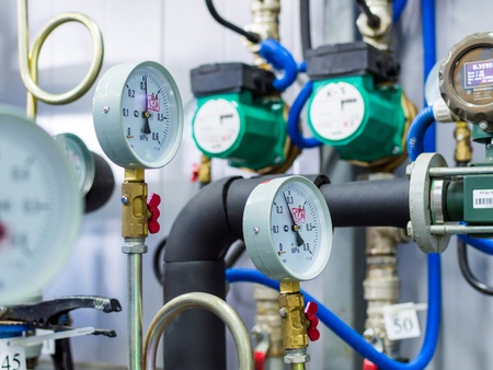 Close up of manometer, pipe, flow meter, water pumps and valves of heating system in a boiler room Stock Photo