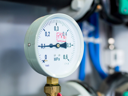 Close up of pressure meter, manometer, pipe, flow meter and faucet valves of heating system in a boiler room