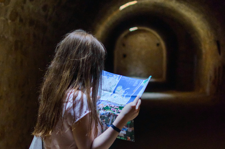 Girl hiker read a map into the dungeon.