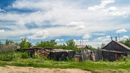 Old wooden house in russian village under the blue sky with clouds