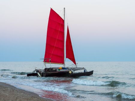 Seal boat with red sail on sunset in Black sea
