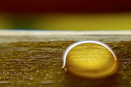 Water drop on a wooden surface. Macro shot with low depth of field.