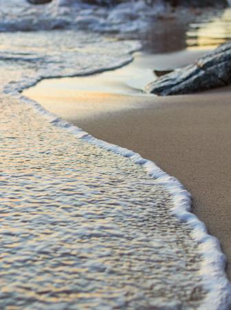 Wave of the sea on the sand beach. Seashore of Phuket on sunset
